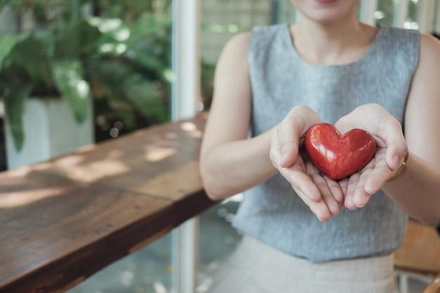 Mulher asian, segurando, coração vermelho, seguro saúde Foto Premium