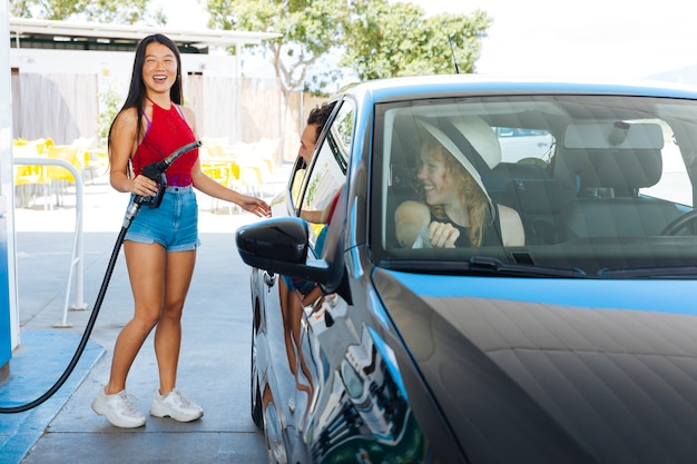 Mulher asian, segurando, gás, bocal, e, abertura, tanque, enquanto, amigos, sentando, carro Foto gratuita