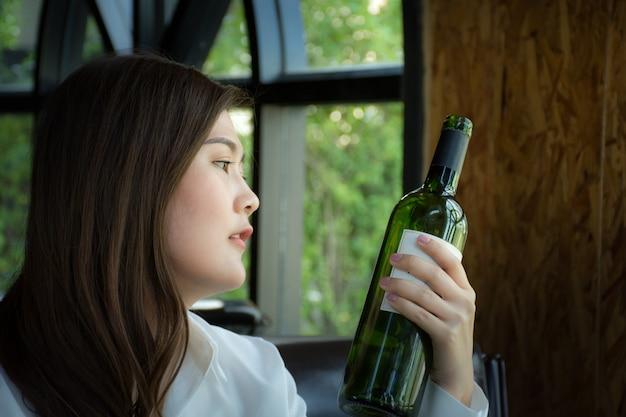 Mulher asian, segurando, um, garrafa vinho, /, mulher, selecionar, um, garrafa vinho, em, restaurante Foto Premium