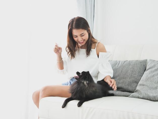 Mulher asian, tocando, com, cão pequeno, cor preta, em, sala de estar, estilo vida, menina, com, animal estimação Foto Premium