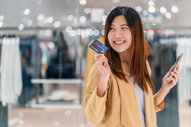 Mulher asian, usando, cartão crédito, com, telefone móvel, para, shopping online, em, loja de departamentos Foto Premium