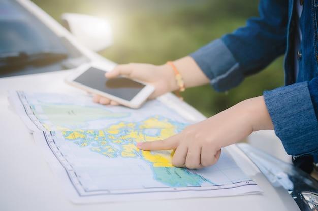 Mulher asian, usando, smartphone, e, mapa, entre, dirigindo carro, ligado, viagem estrada Foto Premium