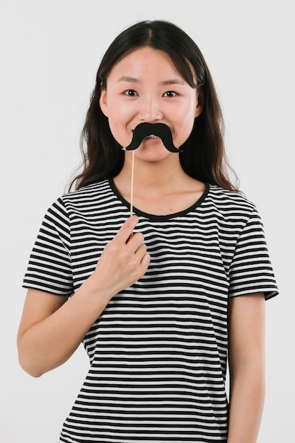 Mulher asiática a experimentar um bigode falso Foto gratuita
