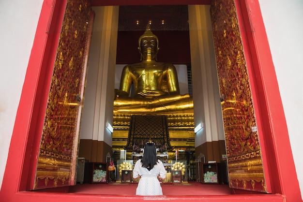 Mulher asiática a pagar respeito à estátua de buda em ayutthaya, tailândia. Foto Premium