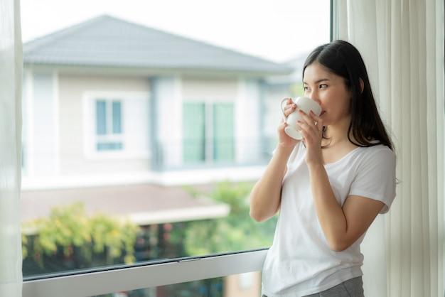 Mulher asiática acorda em sua cama totalmente descansada e abre as cortinas no peitoril da janela e olhando pela janela Foto Premium