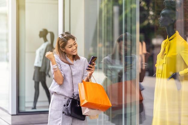 Mulher asiática alegre quando usando o telefone móvel inteligente para verificar a ordem de compra on-line é Foto Premium