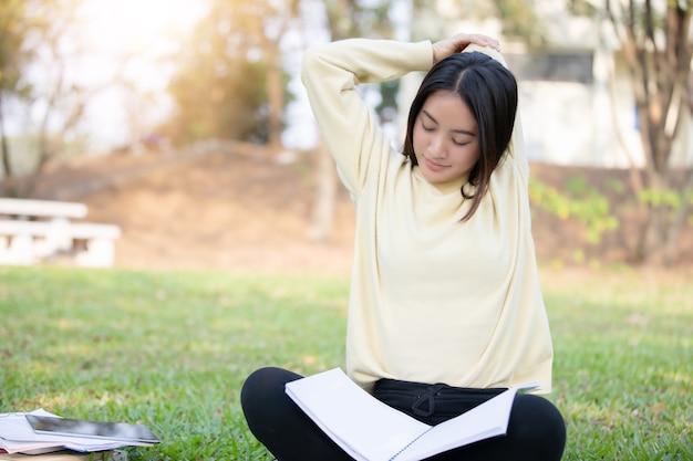 Mulher asiática, alongamento e sentado na grama verde depois de ler o livro e trabalhar duro Foto Premium