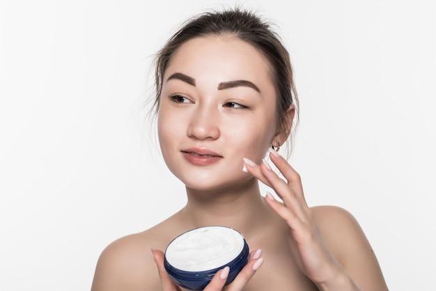 Mulher asiática, aplicar creme cosmético no rosto facial de cuidados com a pele isolado na parede branca Foto gratuita