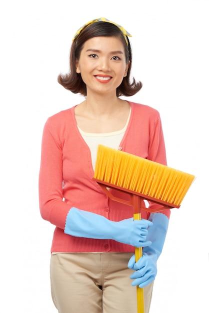 Mulher asiática atraente com vassoura Foto gratuita