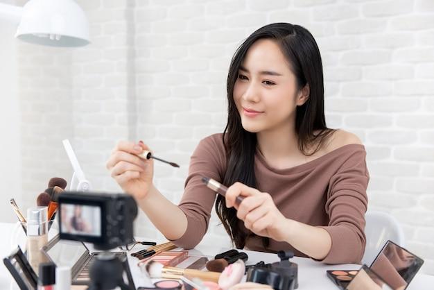 Mulher asiática beleza vlogger fazendo maquiagem cosmética tutorial vídeo Foto Premium