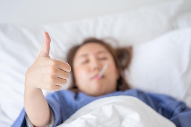 Mulher asiática bonita a hipotermia foi medida pela febre. deite na cama para dar Foto Premium