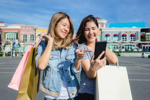 Mulher asiática bonita atrativa que usa um smartphone ao comprar na cidade Foto gratuita