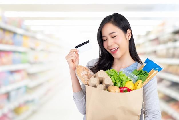 Mulher asiática bonita compras mantimentos com cartão de crédito no supermercado Foto Premium