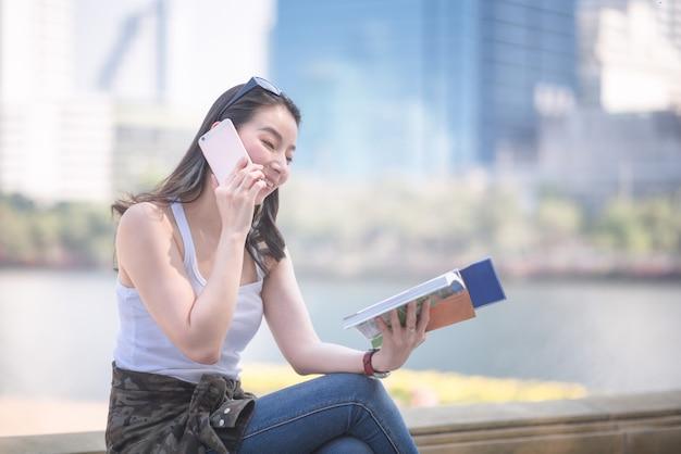 Mulher asiática bonita do turista que lê o guia do curso que procura para pelo ponto sightseeing dos turistas. Foto Premium