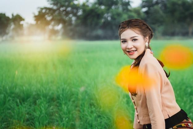 Mulher asiática bonita no vestido local sentado e desfrutar natural na ponte de bambu no campo de arroz Foto Premium