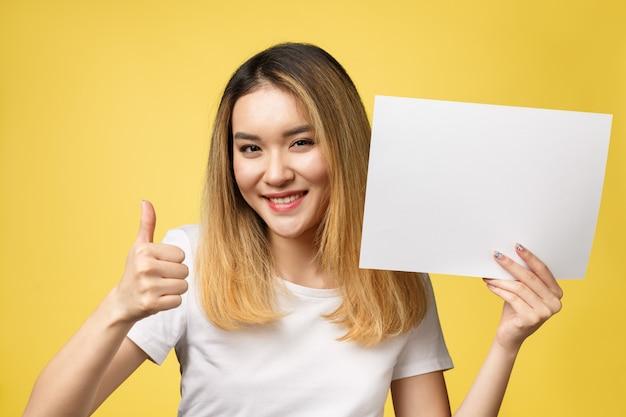 Mulher asiática bonita nova atrativa do estudante que prende o livro branco em branco. Foto Premium