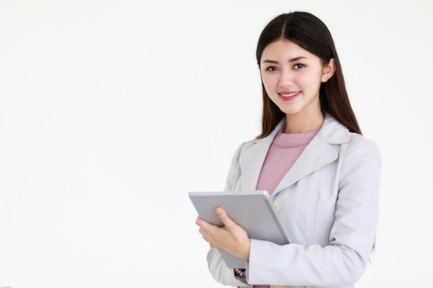 Mulher asiática bonita nova com cabelo preto longo que está na frente do fundo branco Foto Premium