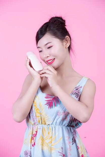 Mulher asiática bonita que guarda uma garrafa do produto em um fundo cor-de-rosa. Foto gratuita