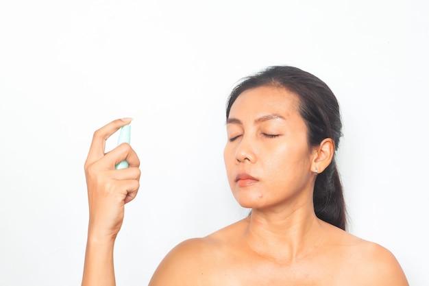Mulher asiática bonita que pulveriza a água mineral em sua face. conceito de beleza e saúde Foto Premium
