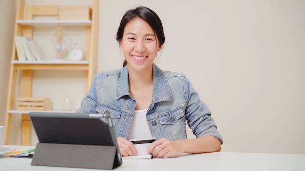 Mulher asiática bonita que usa a tabuleta que compra a compra em linha pelo cartão de crédito quando vestir o assento ocasional na mesa na sala de visitas em casa. Foto gratuita