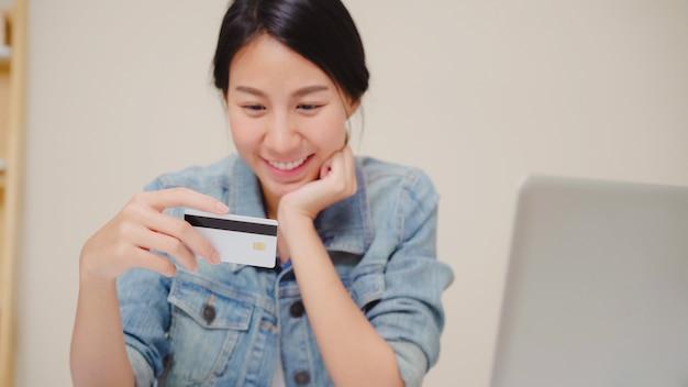 Mulher asiática bonita que usa o portátil que compra a compra em linha pelo cartão de crédito quando vestir o assento ocasional na mesa na sala de visitas em casa. Foto gratuita