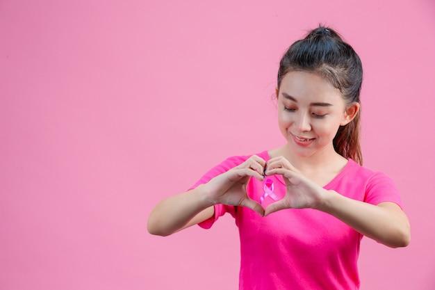 Mulher asiática branca, vestindo uma camisa rosa forma de coração feito à mão em um rosa. Foto gratuita