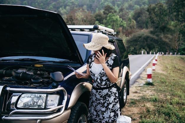 Mulher asiática chamando reparador ou pessoal de seguros para corrigir um problema de motor de carro em uma estrada local Foto gratuita