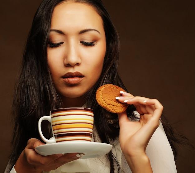 Mulher asiática com café e biscoitos. Foto Premium