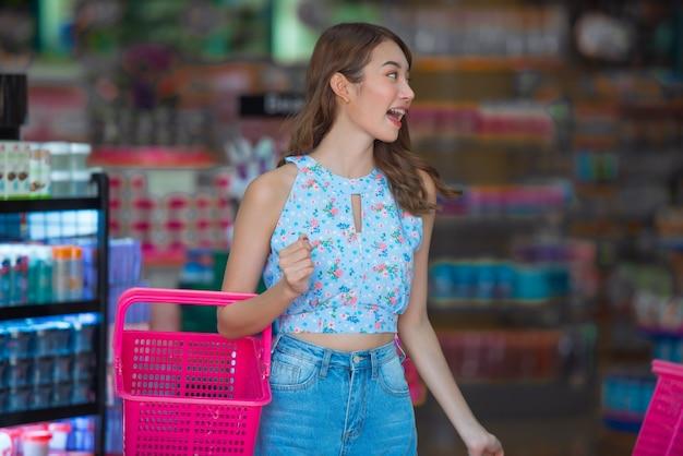 Mulher asiática com coisa de compra da cesta na loja da beleza. Foto Premium