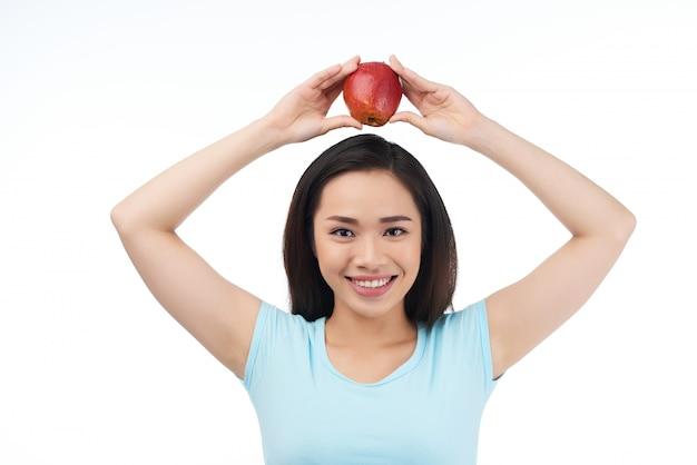 Mulher asiática com maçã vermelha Foto gratuita