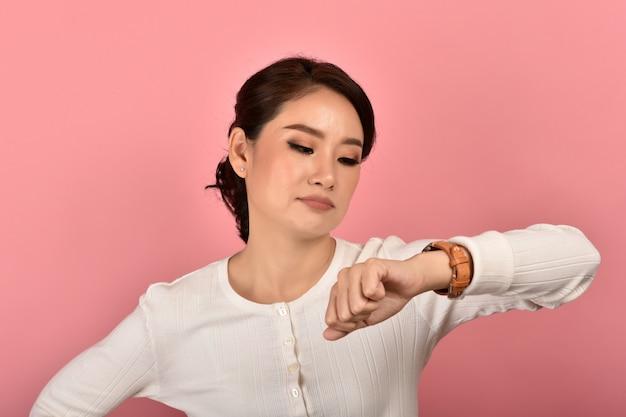 Mulher asiática com raiva e chateada esperando por alguém, mulher olhando para o relógio de pulso irritado por nomeação tardia, responsabilidade de tempo. Foto Premium
