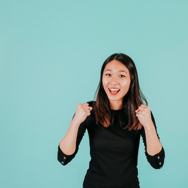 Mulher asiática comemorando sucesso Foto gratuita