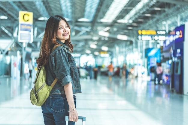 Mulher asiática da beleza que viaja e que guarda a mala de viagem no aeroporto. Foto Premium