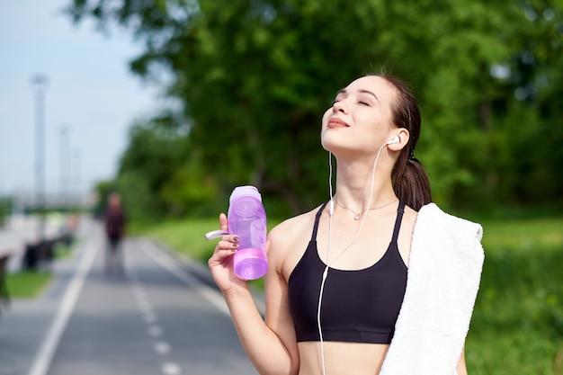 Mulher asiática de aptidão com garrafa de água e toalha após a execução de treinamento no parque de verão Foto Premium