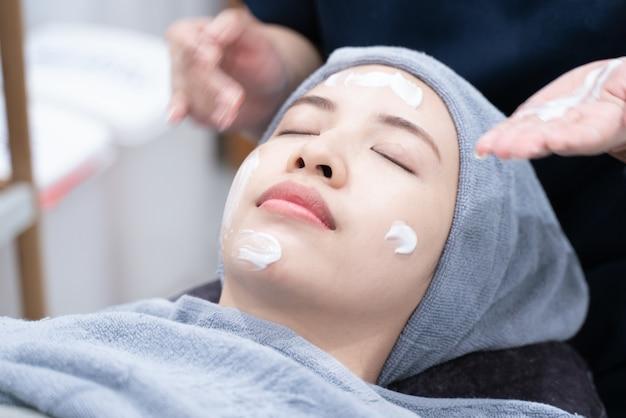 Mulher asiática de limpeza da pele facial no salão de beleza ou clínica Foto Premium