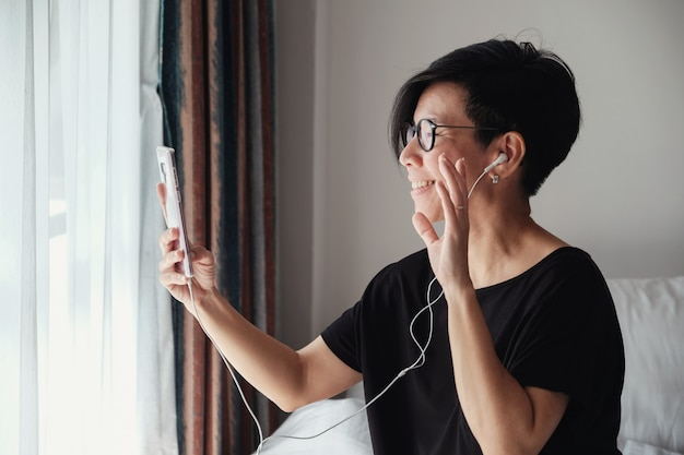 Mulher asiática de meia idade fazendo vídeo chamando em casa Foto Premium