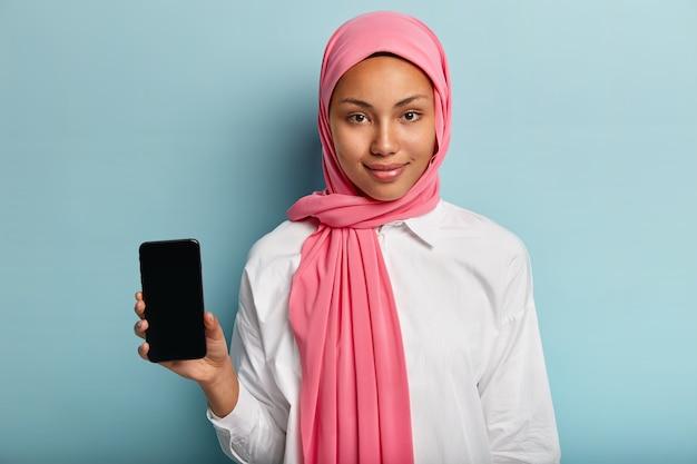 Mulher asiática de pele escura com lenço rosa, veste camisa branca, segura o telefone celular com simulação de tela para inserção de imagem ou texto, isolada sobre a parede azul. foco seletivo. tecnologia, cultura, propaganda Foto gratuita