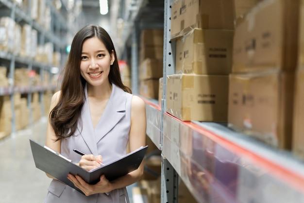 Mulher asiática de sorriso esperta que trabalha no armazém de armazenamento. Foto Premium