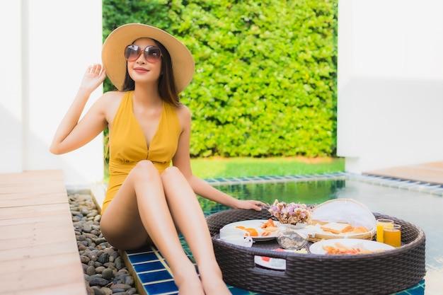 Mulher asiática, desfrutando com café da manhã na piscina Foto gratuita