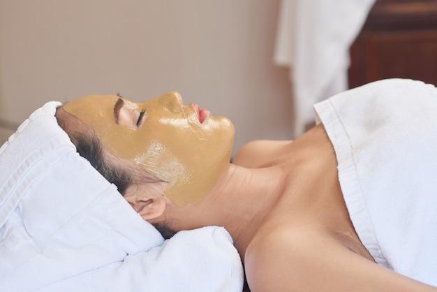 Mulher asiática, desfrutando de procedimento de skincare Foto gratuita