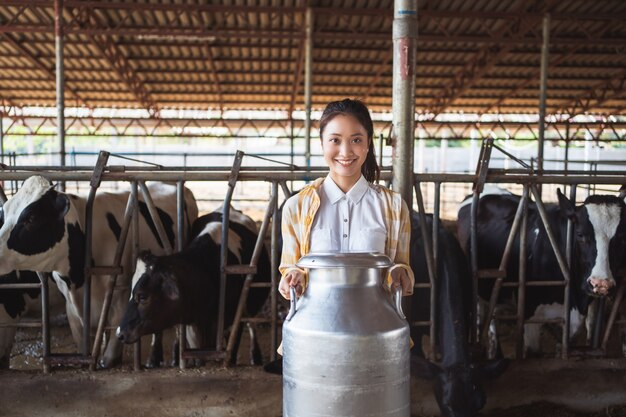 Mulher asiática do agricultor retrato está segurando um recipiente de leite em sua fazenda. Foto Premium