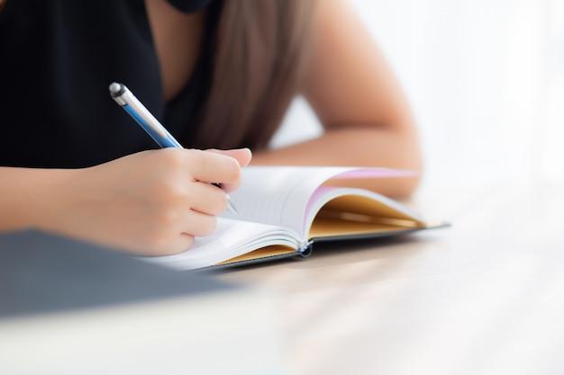 Mulher asiática do close up da mão que senta o estudo e que aprende o caderno da escrita Foto Premium