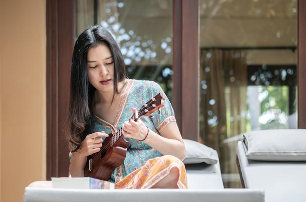 Mulher asiática do close up que joga o ukulele no sofá no terraço Foto Premium