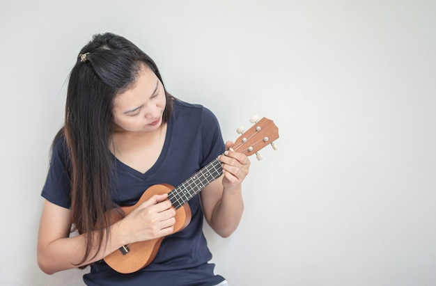Mulher asiática do close up que joga o ukulele Foto Premium