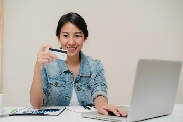 Mulher asiática do negócio esperto bonito que usa o computador ou o portátil que compram a compra em linha pelo cartão de crédito quando vestir o assento ocasional esperto na mesa na sala de visitas em casa. Foto gratuita