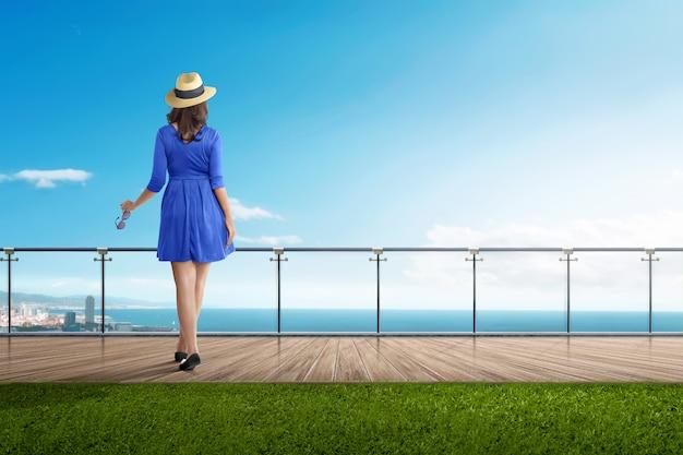 Mulher asiática do viajante de vista traseira em pé na varanda Foto Premium