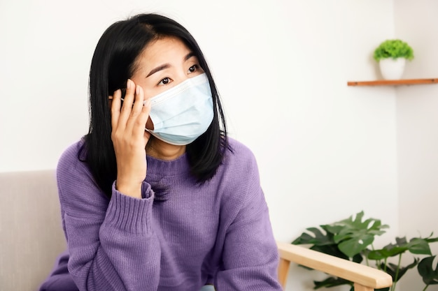 Mulher asiática doente com máscara e dor de cabeça Foto Premium