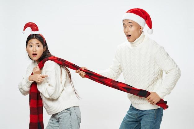 Mulher asiática e homem com chapéus de papai noel posando juntos Foto Premium