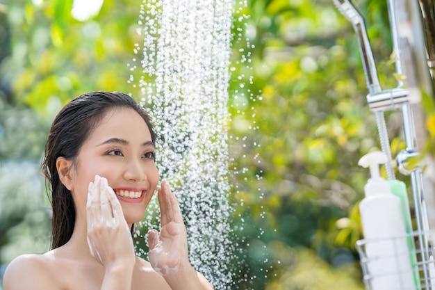 Mulher asiática, ela toma banho e lava os cabelos lá fora. ela está descansando no resort. Foto gratuita