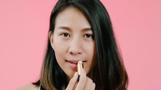 Mulher asiática elegante bonita nova que aplica a composição dos bordos com a escova cosmética na roupa ocasional sobre o tiro cor-de-rosa do estúdio do fundo. Foto gratuita